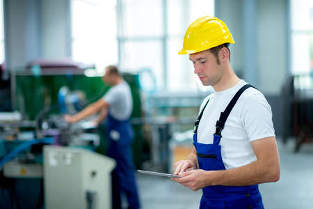young worker in factory using tablet pc 版權商用圖片 - 37302878