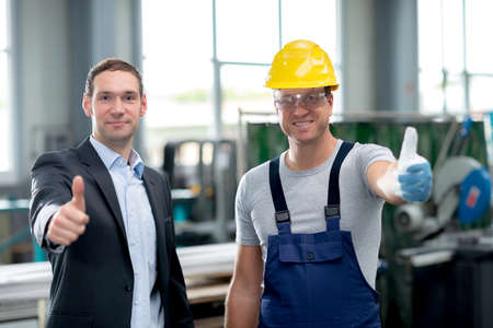good team in factory with thumbs up Stock Photo