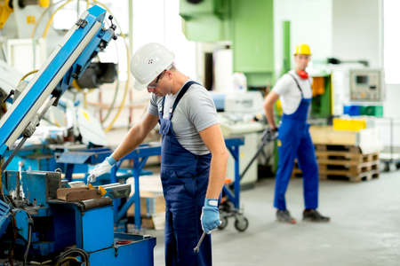 worker in protective clothing in factory using machine Stock Photo