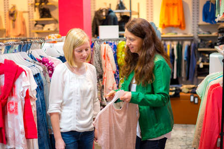 discontent: two women in the clothes shop looking for outfit