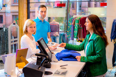 young woman and man in the clothes shop over the counter photo