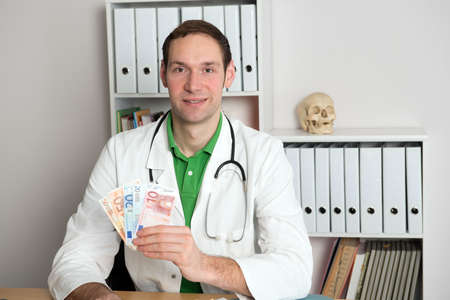 doctor money: young friendly doctor in her office with money Stock Photo