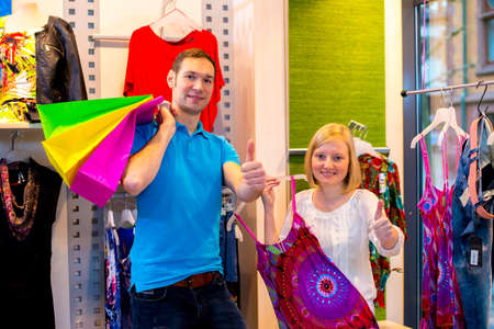 young couple in the clothes shop looking for a new dress and keeping up the thumb photo