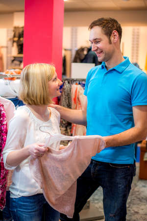 young couple in the clothes shop looking for a new dress photo