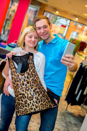 young couple in the clothes shop looking for a new dress and take a selfie photo