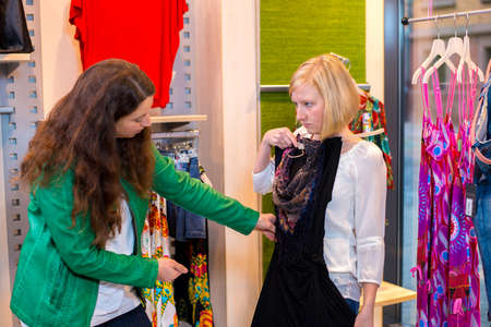 two woman in the clothes shop looking for outfit photo