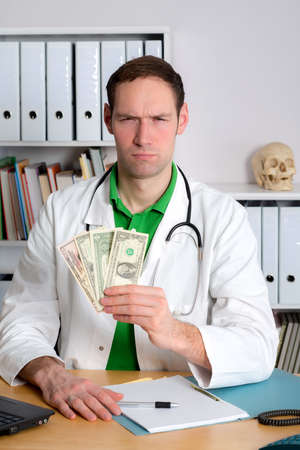 doctor with dollars: young doctor in his office with dollars is angry