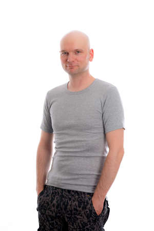 bald head: man with bald head in gray shirt is looking friendly in to the camera