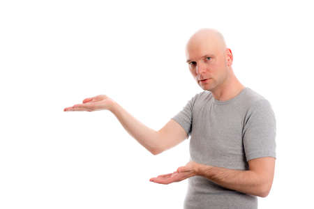 skinhead: young man with bald head in gray shirt is pointing to the side Stock Photo