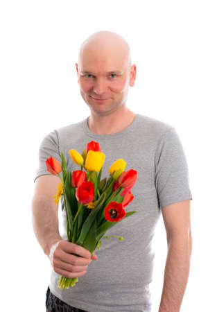skinhead: young man with bald head and bunch of tulips in front of white background