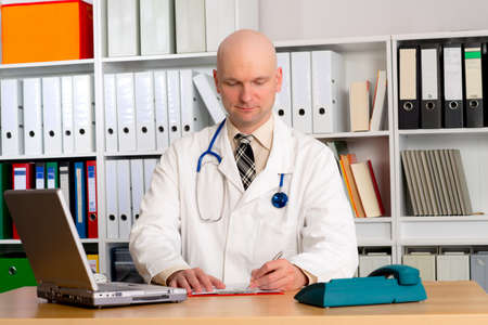 skinhead: young family doctor in his office is writing Stock Photo