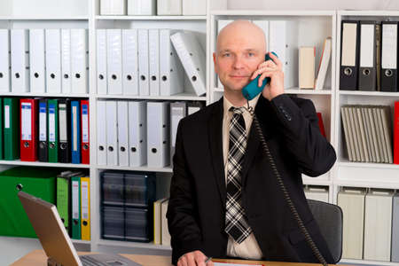 bald head: young businessman with bald head in the office is calling