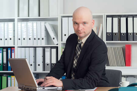 bald head: young businessman with bald head in the office is looking in to the camera Stock Photo