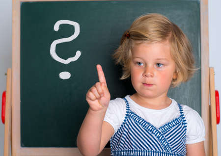 forefinger: clever girl in front of black board with forefinger up Stock Photo