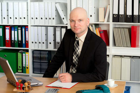 skinhead: young businessman in the office is looking friendly in to the camera Stock Photo