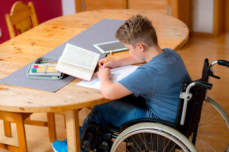 homework: disabled boy in wheelchair doing homework