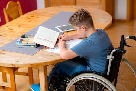 tarea escolar: niño discapacitado en silla de ruedas haciendo los deberes