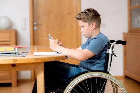 silla de ruedas: niño discapacitado en silla de ruedas haciendo la tarea y en el chat en internet