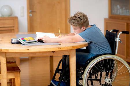 deberes: ni�o discapacitado en silla de ruedas haciendo los deberes