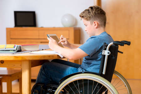 handicapped person: disabled boy in wheelchair doing homework and chatting in the internet Stock Photo