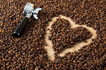 crema: heart in a lot of coffee beans with heart with portafilter Stock Photo