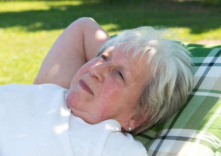 gray haired: gray haired female senior is relaxing in the garden