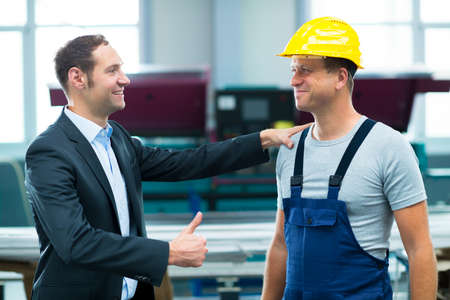 young boss is lauding worker in factory