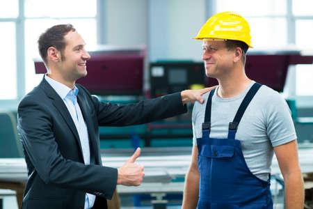 patron: joven jefe se elogiaba trabajador en la fábrica Foto de archivo
