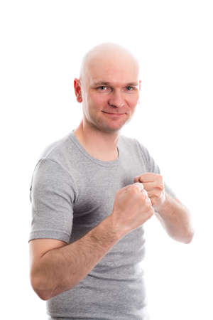 skinhead: funny young man with bald head and fist- hands grining in to the camera Stock Photo