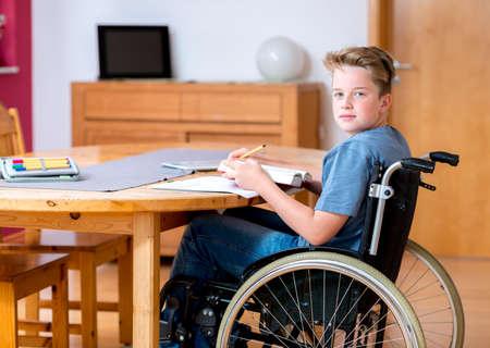 personen: gehandicapte jongen in een rolstoel huiswerk
