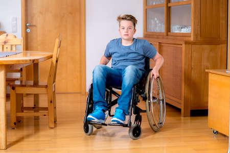 persona triste: ni�o discapacitado en silla de ruedas en su casa en la sala de estar Foto de archivo