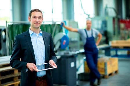 supervisores: jefe joven con el trabajador en el fondo en su fábrica Foto de archivo