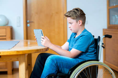disabled boy in wheelchair chatting in the internet with tablet PC 版權商用圖片 - 42177670