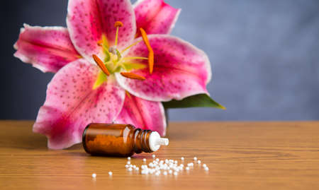 globuli: homeopathic globules on wooden ground with lilly blossom