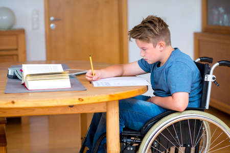 discapacidad: niño discapacitado en silla de ruedas haciendo los deberes