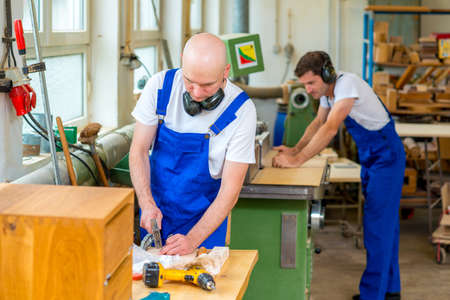carpenter: two young worker in blue dungarees in a carpenters workshop Stock Photo