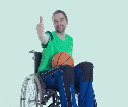 paraplegico: joven hombre discapacitado en silla de ruedas está haciendo deporte con la bola y el pulgar Foto de archivo