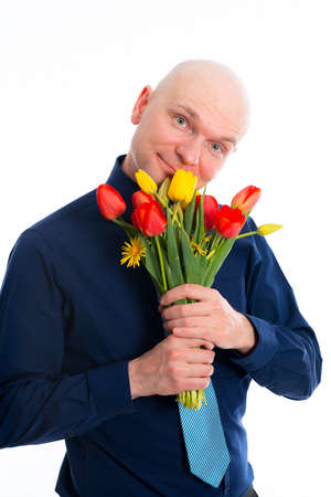 skinhead: young man with bunch of tulips in front of white background