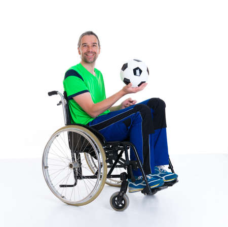 young disabled man in a wheelchair is doing sport with ball