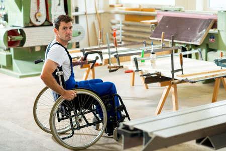 discapacidad: trabajador con discapacidad en silla de ruedas en el taller de un carpintero Foto de archivo