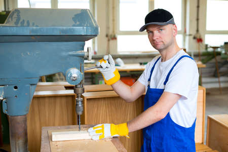 drilling machine: worker with dark cap in a carpenters workshop using drilling machine