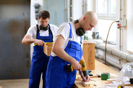bib overall: two men in workwear in a carpenters workshop