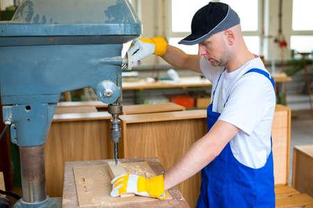 drilling machine: worker with dark cap in a carpenters workshop using drilling machine
