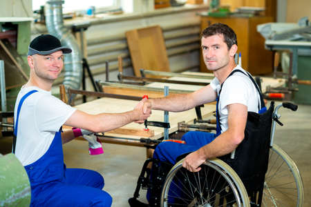 disabled worker in wheelchair in a carpenters workshop with his colleague Stock Photo