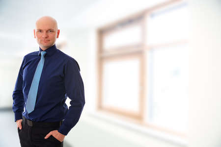 skinhead: young businessman with bald head in front of white background