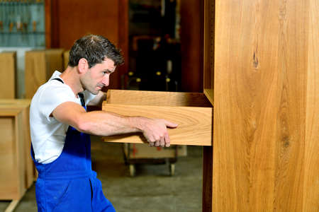 bib overall: worker in blue dungarees in a carpenters workshop