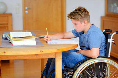 disability: disabled boy in wheelchair doing homework