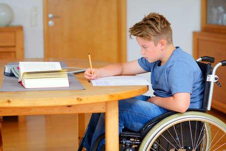 discapacidad: ni�o discapacitado en silla de ruedas haciendo los deberes