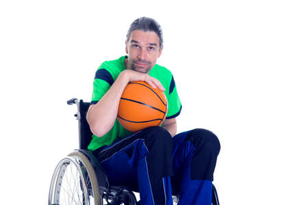 disability insurance: young disabled man in a wheelchair is doing sport with ball