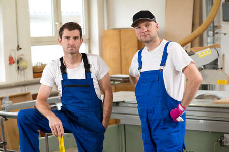 bib overall: two worker in blue dungarees in a carpenters workshop Stock Photo